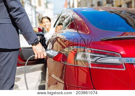 Refueling of the car. Handsome confident male businessman holding a fuel nozzle and putting in into the car while refilling it with petrol
