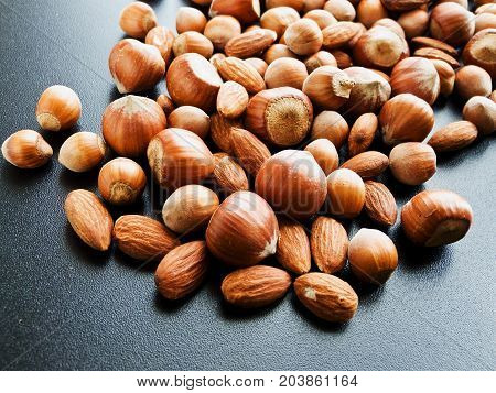 Hazelnuts and almond on the black. Shallow dof.