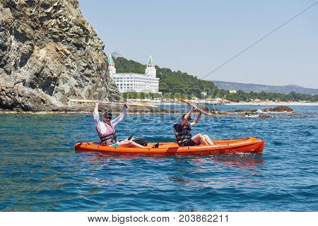Boat kayaking near cliffs on a sunny day. Kayaking in a quiet bay. Amazing views. Travel, sports concept. Lifestyle. A happy family