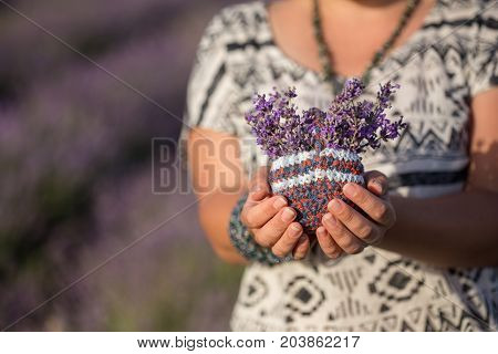 Woman in black and white ornamented ethnic wear holds small knitted basket with bunch of blooming lavender flowers in hands under summer sunlight. Shallow dof. Focus on basket.