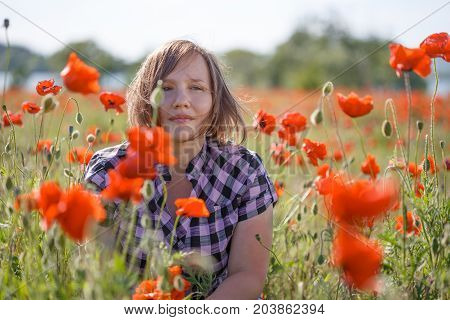 Young beautiful smiling woman in checkered chemise with short blonde hair flying on wind sits on summer blooming poppy flower field.