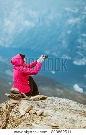 Tourism vacation and travel. Female tourist taking photo with camera enjoying mountains landscape from Dalsnibba viewpoint Norway Scandinavia.