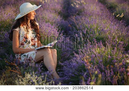 Romantic Woman Sits With Book On Lavender Field