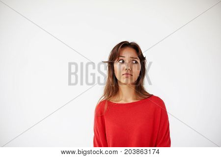 Beautiful young brunette woman of mixed race appearance frowning her eyebrows and looking sideways with puzzled suspicious expression on her face. Embarrassment confusion and perplexity concept