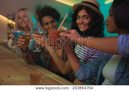 selective focus of multicultural friends with cocktails having party together in bar