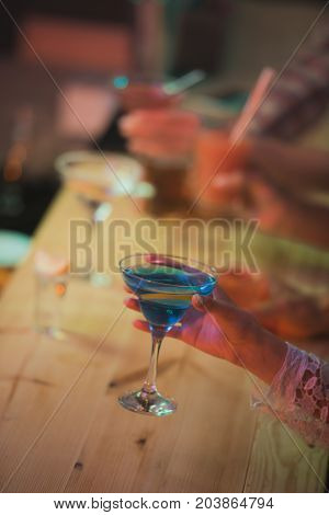 cropped shot of female hand with cocktail in bar