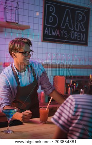 selective focus of young smiling barman at counter in bar
