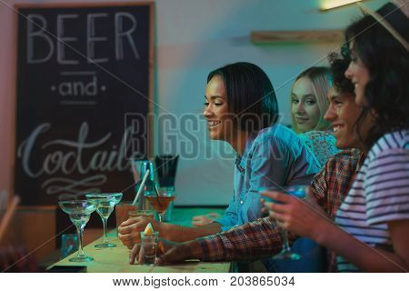 side view of smiling multicultural friends spending time together in bar