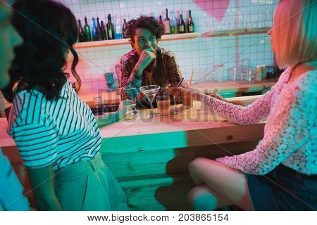 selective focus of cheerful african american barman and visitors at counter in bar