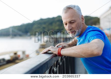 Checking results. Pleasant handsome senior man standing on the bridge, resting after jogging and looking at his smart watch, checking the number of kilometers of a run