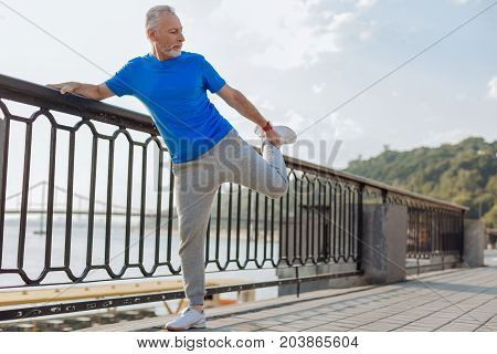 Sports lover. Charming senior man standing on the bridge and stretching his leg muscles while warming up before his morning run