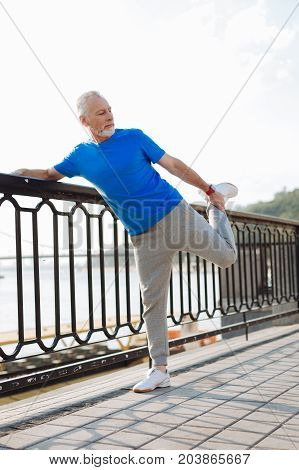 Love sports. Pleasant athletic senior man standing on the bridge and stretching his leg muscles during morning run