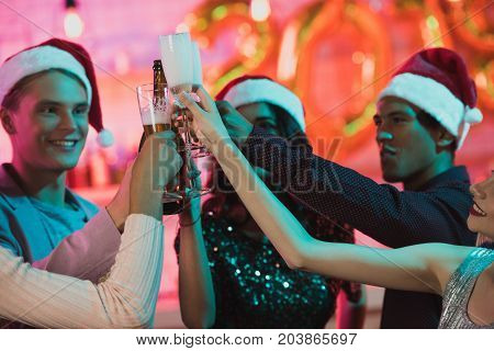 happy multiethnic friends clinking glasses of champagne while celebrating new year together
