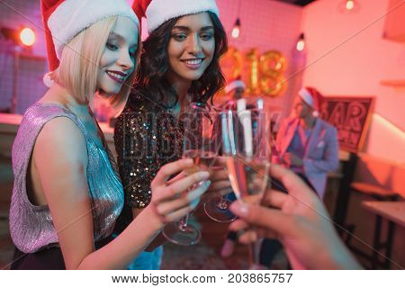 partial view of smiling friends clinking glasses of champagne while having new year party