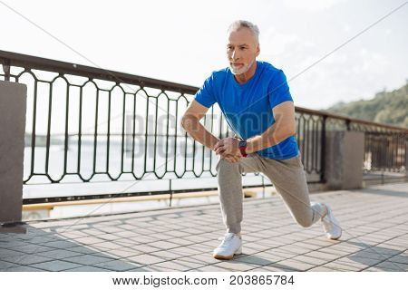 Important exercises. Handsome young man doing lunges, stretching himself during his morning run on the bridge