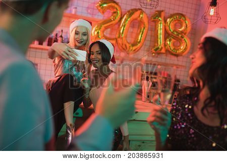 smiling multicultural women taking selfie during new year party with friends