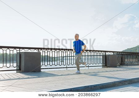 Morning run. Energetic senior man in a blue t-shirt keeping fit and running down the bridge in the morning