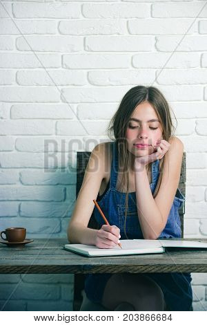 Young woman sitting at wooden table. Teenager student in jean pinafore on white brick wall. Girl writing with pencil in notebook. Study and learning concept. Education and knowledge