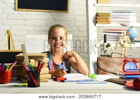 Kid with colorful stationery on white wall background. Girl with happy face does homework. Childhood and back to school concept. Pupil with books and school supplies.