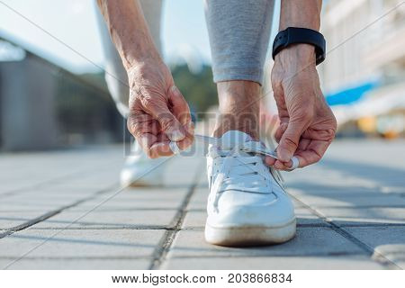 Necessary adjustment. The close up of hands of a sporty elderly woman tying shoelaces on her sneaker while jogging in the morning