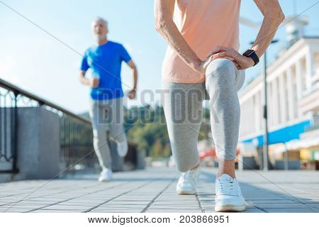 Warming up thoroughly. The close up of an athletic elderly woman doing lunges in the streets while a man in the blue t-shirt running past her