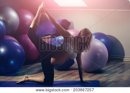 Mother with big belly in gym with fit balls. Pregnancy and fertility. Prenatal fitness yoga and healthy lifestyle. Motherhood and maternity concept. Pregnant woman stretching on mat.