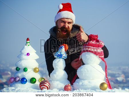 Santa Man Putting Hat On Snowman And Showing Ok Gesture