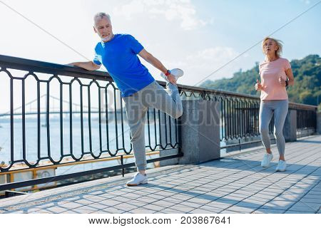 Everyday exercising routine. Athletic senior man holding on to the bridge balustrade and performing stretching exercises while his wife jogging past him