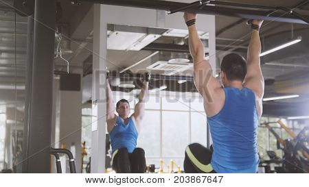 Young man athlete doing pull-up bar abdominal exercise in gym, wide angle