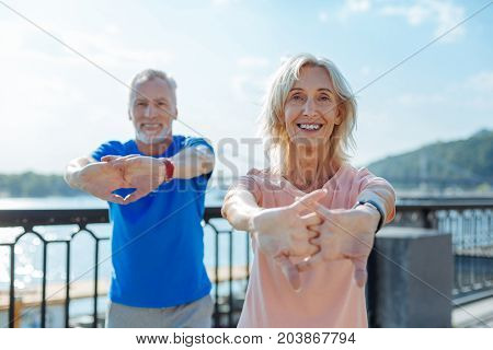 Effective warm-up. Joyful energetic senior man and woman holding hands in a lock and stretching while warming-up before their morning run