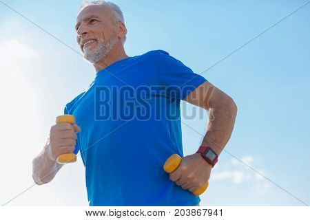 Full of energy. Handsome elderly bristled man holding dumbbells in both hands and running with them in the city
