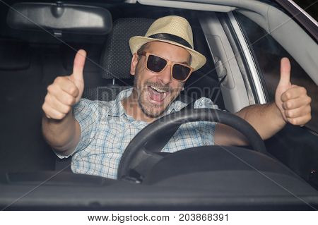 Portrait of young man on driver seat wearing hat and sunglasses and showing thumbs up. On the road and travel concepts.
