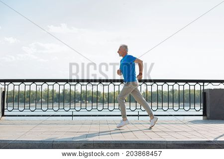 Brisk jogging. The side view of athletic elderly man jogging down the bridge while training thoroughly and keeping fit