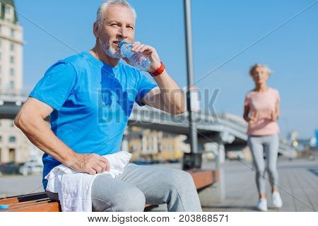 Staying hydrated. Handsome elderly man sitting on the bench, holding a towel and drinking water after his morning run while a woman jogging in the background