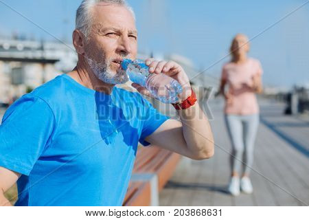 Living healthy. Pleasant senior man sitting on the bench, drinking water and resting after a morning run while a woman jogging in the background