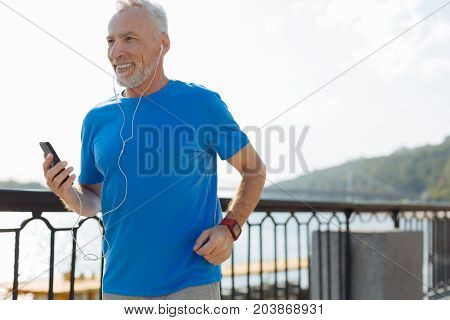 Music inspires. Upbeat elderly man running down the bridge and listening to the music in the headphones while smiling happily
