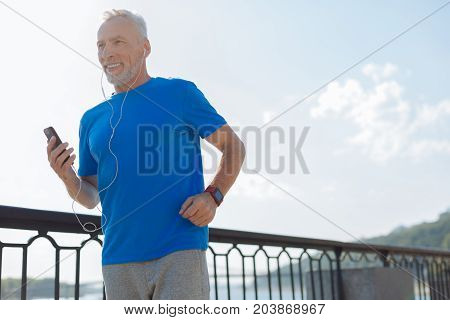 Music motivates. Handsome athletic senior man listening to the music in the headphones while having his morning run