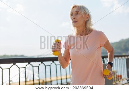 Working out with pleasure. Pretty elderly woman jogging down the bridge while holding a pair of yellow dumbbells
