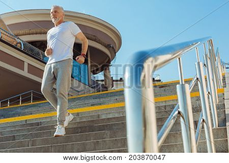 In a rush. Athletic fit senior man in a sporty outfit going down the stairs in a quick pace, being in a rush