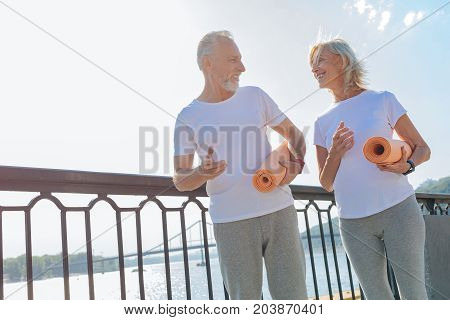 Enjoy training together. Cheerful athletic elderly couple walking down the bridge and holding yoga mats while planning to practice yoga