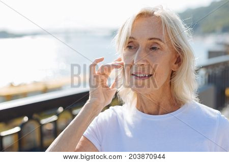 Dreamy look. The close up of a charming elderly woman standing on the bridge, tidying up her hair while looking dreamily into the distance