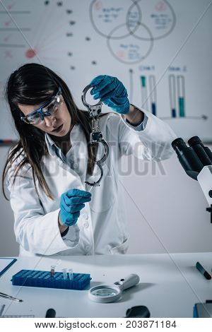Forensic Science. Female Analyzing Samples In The Lab. Toned Image