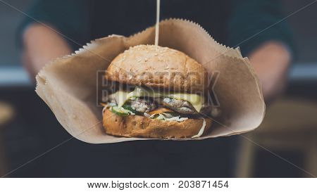 Street fast food festival, hamburger cooked at barbecue outdoors. Cookout american bbq food, closeup in chef's hand on foil, closeup