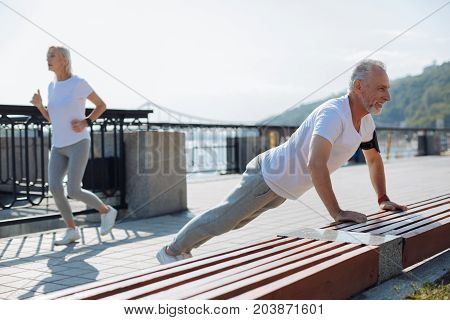 Sporty family. Well-built elderly man doing push-ups from the bench while his slender wife jogging down the bridge