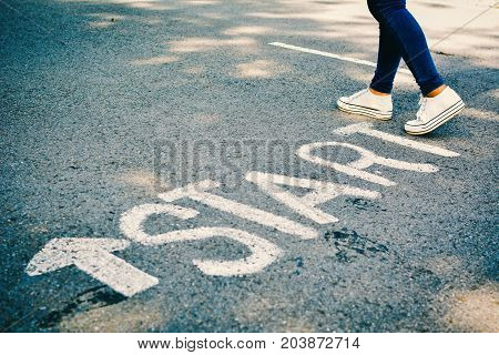 Feet of women with start word on road concept keep going hipster tone