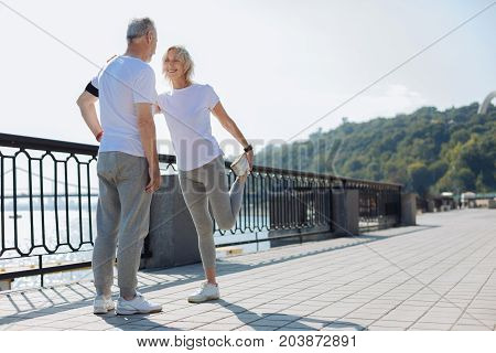 Thanks for support. Joyful slender senior woman doing stretching exercises while her beloved husband providing her with balance, functioning as a pivot