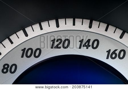 Closeup of the speedometer in silver blue and black from the interior of a vehicle