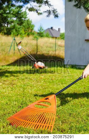 Woman Using Rake To Clean Up Garden Lawn
