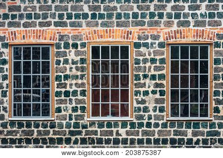 Brick Wall with large windows from an old indusrial building made of cinder or slag stones