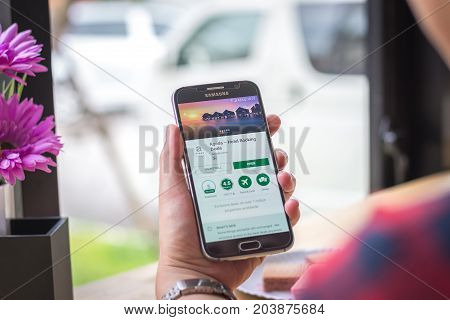Chiang Mai, Thailand - September 12, 2017: Samsung Galaxy S6 smartphone launches agoda application on the desk screen at the coffee shop.